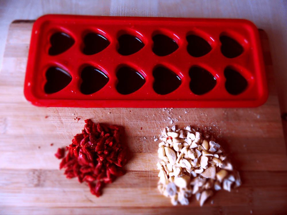 Once it's melted into a nice liquid, pour the chocolate into a heat resistant mold. Feel free to add fillings of your liking. I went for some chopped goji berries and cashews